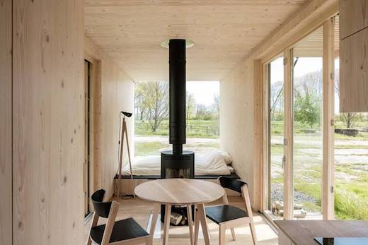 the interior walls are paneled with timber plates that give the home a cozy warm feel
